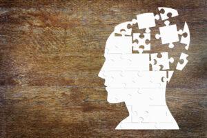 zarys ludzkiej głowy ułożony z puzzli, niektórych brak