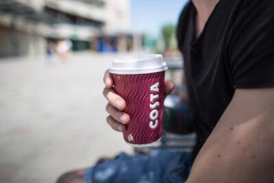 mężczyzna trzymający kubek z kawą z costa coffee