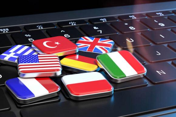 Na czarnej klawiaturze leżą małe prostokąciki przedstawiające flagi, m.in. Polski, Francji, Włoch czy USA.