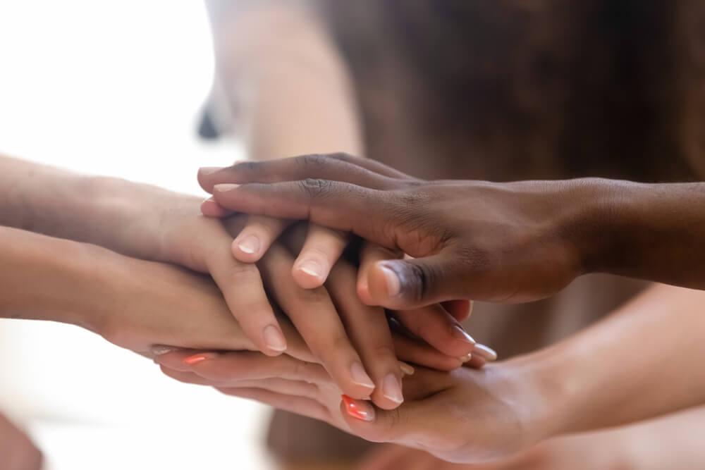 Dłonie o różnym kolorze skóry, które się na siebie nakładają.