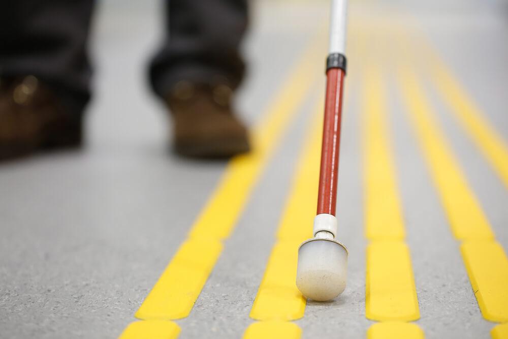 Kawałek laski, która jest prowadzona po ścieżce dla niewidomych. W oddali widać także buty osoby prowadzącej laskę.